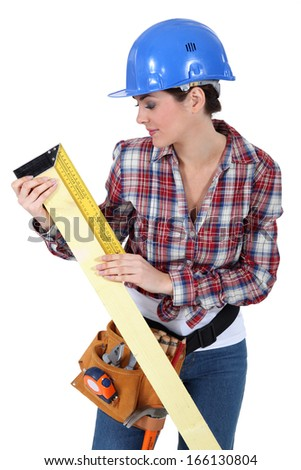 craftswoman measuring a board - stock photo
