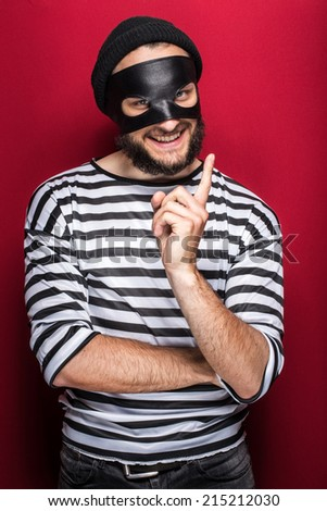Crafty bandit smiling and threaten with finger on red background - stock photo