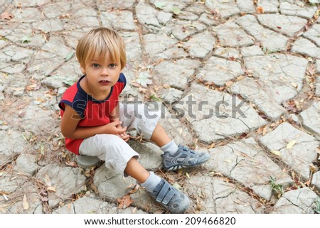 Crafty kid sitting on the cracked earth and looking up.