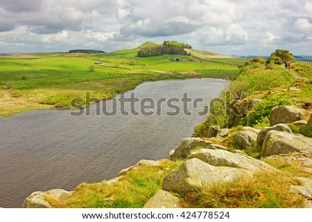 Crag Lough is situated in some of the most iconic country along Hadrian's Wall, an isolated farm can just be seen in the distance, Northumberland National Park, England, UK - stock photo