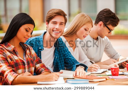 Cramming before an exam. Joyful young man smiling and looking at camera while sitting with his friends at the wooden desk outdoors