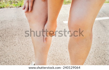 Cramps in leg calves or sprain calf on triathlete runner sports injury with running woman