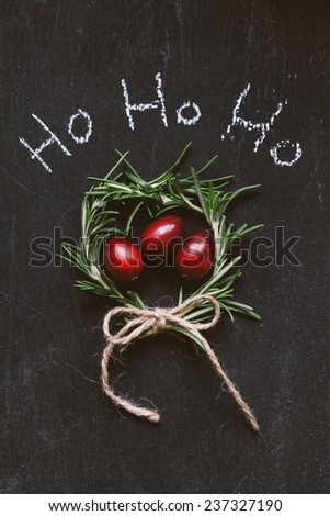 Cranberries in a herbs wreath on a slate background with an inscription in chalk Ho ho ho