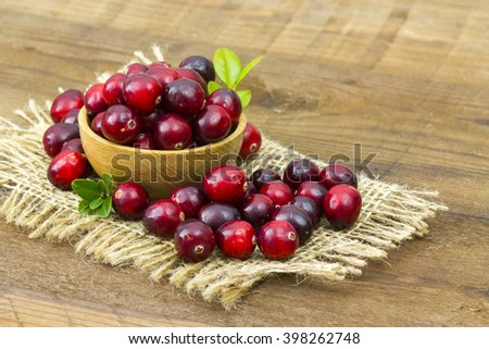 Cranberries in wooden bowl on wooden background - stock photo