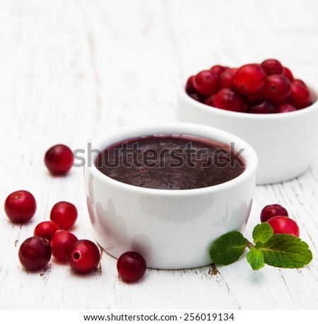 Cranberries jam with fresh berries on a wooden background - stock photo
