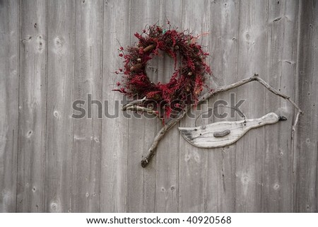 Cranberry colored wreath on an old weathered barn in Bar Harbor Maine.