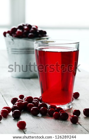 Cranberry juice and berries on a wooden surface - stock photo
