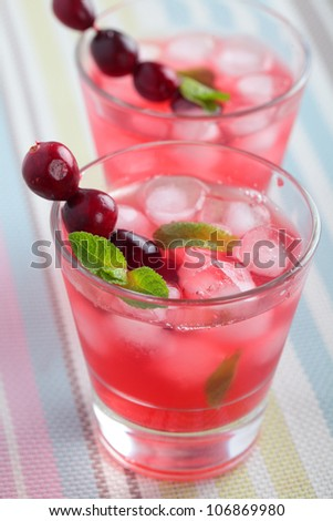 Cranberry juice with berries, ice, and mint - stock photo