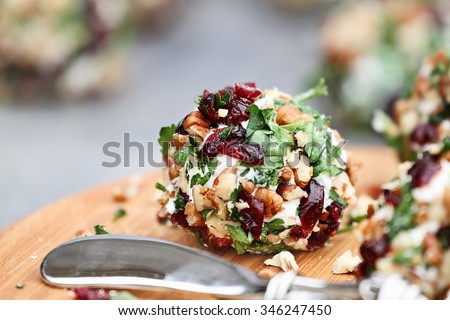 Cranberry nut cheese ball made with cream cheese, goat or feta cheese, parsley, cranberries and chopped pecans over a rustic background. Extreme shallow depth of field with selective focus on center. - stock photo