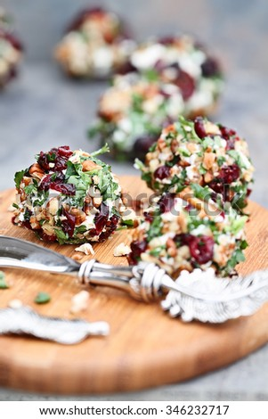 Cranberry nut cheese ball made with cream cheese, goat or feta cheese, parsley, cranberry and pecans over a rustic background. Extreme shallow depth of field with selective focus on center appetizer.