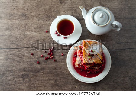 Cranberry Pie for Christmas and tasty tea with foxberry leafs are on wooden table. - stock photo