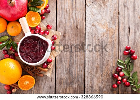 Cranberry sauce in ceramic saucepan on dark background - stock photo