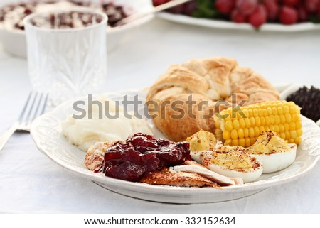 Cranberry Sauce over roast Thanksgiving turkey with all the fixings. Extreme shallow depth of field. - stock photo