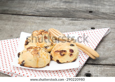 cranberry scone on the white dish, decorate with tablecloth, spoon and fork. However I attend to focus on cranberry more than decorations - stock photo