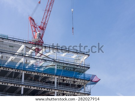 Crane above the iron girder frame of a new building on construction site - stock photo