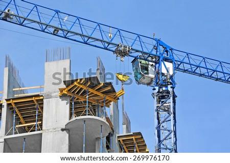 Crane and building construction site against blue sky - stock photo