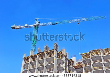 Crane and building construction site against blue sky