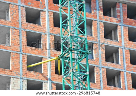 Crane and building construction site with balcony - stock photo