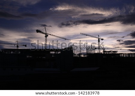crane and construction and sunset sky ,Industrial construction cranes and building silhouettes over sun at sunrise. real estate house and condominium business investment background - stock photo