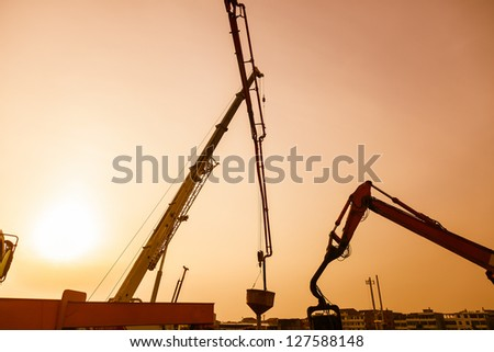 crane and other construction machine in a construction site - stock photo