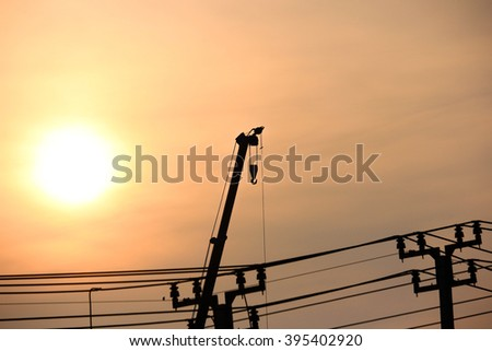crane and the electricity post against a sunset sky with copy space. - stock photo