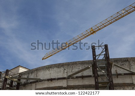 crane and top of construction building over blue sky