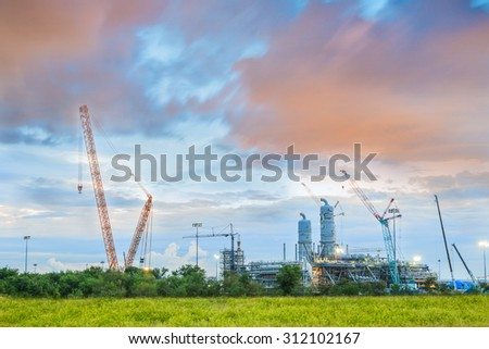 Crane and workers at construction site against blue sky
