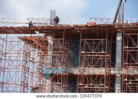 Crane and workers at construction site against blue sky. Thailand - stock photo