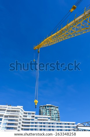 Crane arm nearby to high-rise apartment buildings on sunny day in British Columbia, Canada. - stock photo