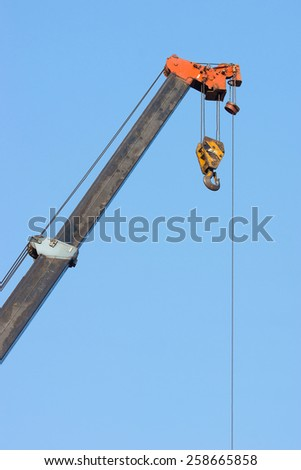 crane boom with hooks with blue sky background. - stock photo