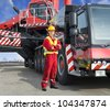 Crane driver, posing next to the huge mobile crane he's operating - stock photo