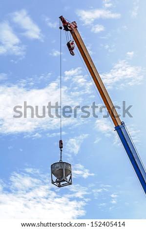 Crane hoist concrete bucket at construction site - stock photo