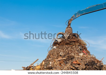 crane holding rusty metal in recycling junkyard - stock photo