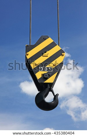 Crane hook with yellow and black stripes hanging, blue sky in background - stock photo
