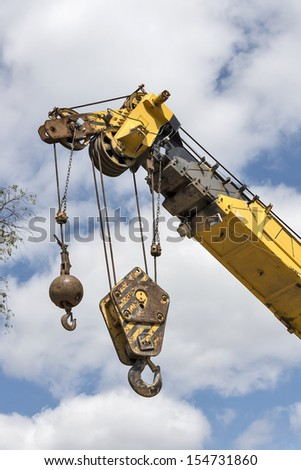Crane hooks on a mobile crane waiting to hoist cargo on a construction site - stock photo