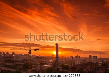 Crane in the construction site under the sunset and city silhouette