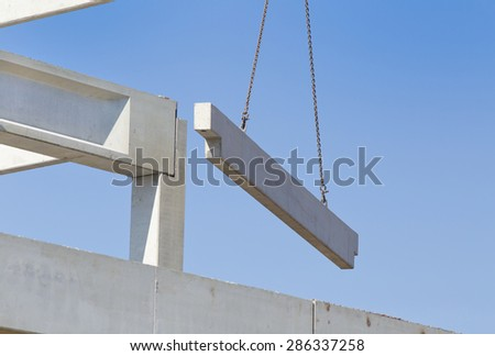 Crane lifting concrete truss for installing in building skeleton - stock photo