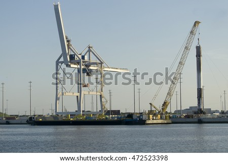 Crane lifting metal canister/Falcon 9/Recovered spacecraft hoisted from barge