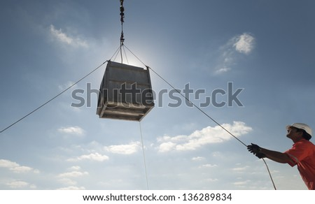 crane lifting operations - men attending tag lines - stock photo
