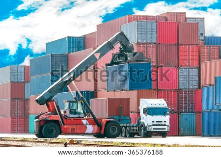 Crane lifting up container in railroad yard beautiful  blue sky background - stock photo