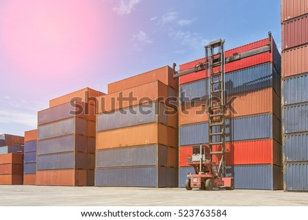 Crane lifting up container in yard.