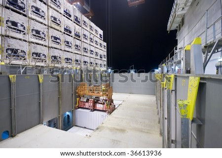 crane lowering a container night operation - stock photo