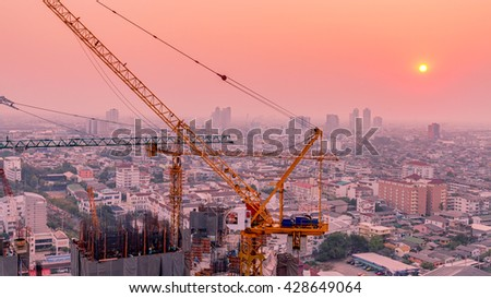 Crane of building during construction on sunset sky in Bangkok city Thailand - stock photo