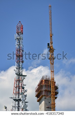 Crane on the construction site and tall antenna tower