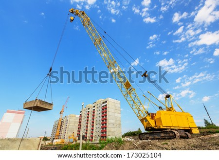 Crane on the construction site beneath blue cloudy sky - stock photo