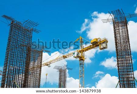 crane operating among metal foundation poles - stock photo