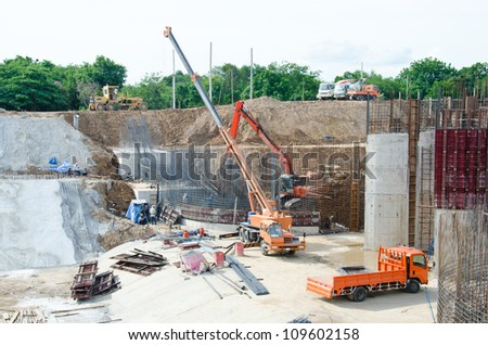 Crane standing on a construction site under construction floodgate. - stock photo