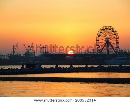 Cranes and a ferris wheel at Kaohsiung harbor at sunset