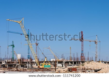 Cranes at a construction site of a new residential area - stock photo