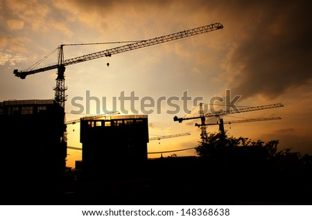 Cranes construction and building silhouette over sun at sunset - stock photo